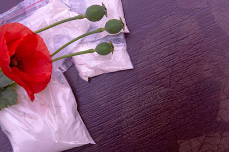 flowers and opium poppy heads next to packages of heroin, soft focus, toning
