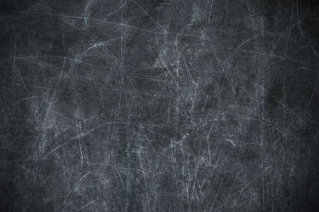 back to school: black chalkboard with blurry traces of white chalk and crayons, minor scratches