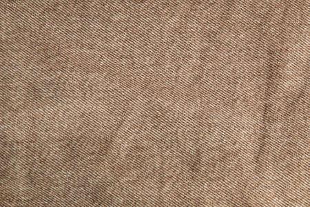 fabric grunge background, real cotton denim brown, wrinkled, frayed, close