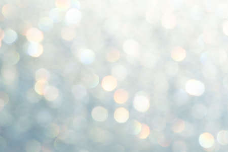 bright glitter background: bokeh effect from many colored lights on frozen glass, toning