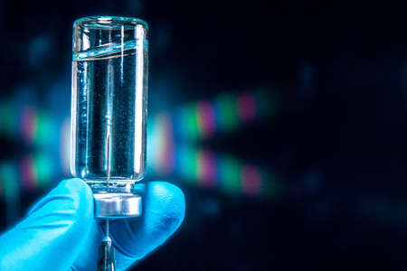 Sars-Kov-2 virus vaccine in a transparent glass ampoule, covered with frost, on a dark background, short focus, toning