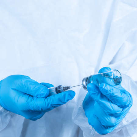 Sars-cov-2 vaccination: a health worker with a vaccine and a syringe in his hands