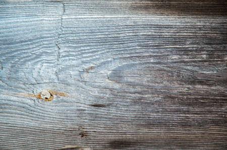 grunge background: sunburnt whitened wood surface close, cracks and dents, toning