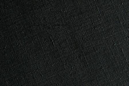 dark creative background: black primed linen canvas, uneven lighting, toning Foto de archivo
