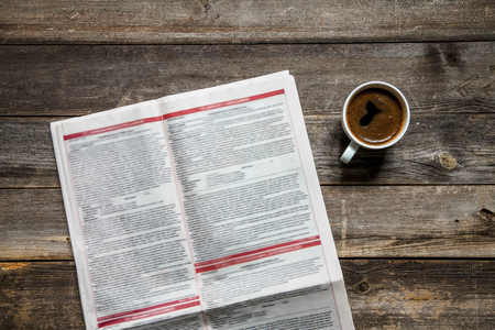 Reading newspaper on wooden background