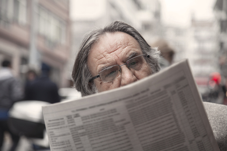 Senior man reading newspaper in outdoors 스톡 콘텐츠