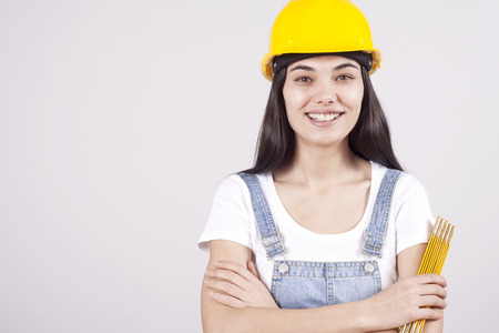Proud serious young woman architect or engineer with arms crossed as professional building supervisor concept isolated on white background