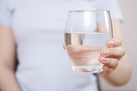 Frau ist Hand, die Trinkwasser auf grauem Hintergrund hält