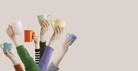 Muchos brazos diferentes levantados sosteniendo una taza de café Foto de archivo