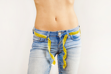 Beautiful woman is abdomen with jeans isolated on gray background
