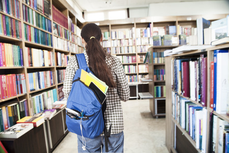 Student with backpack in library Stok Fotoğraf