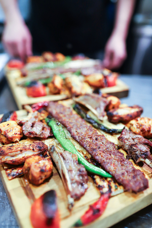 Traditional oriental Adana kebap and shashlik skewer with tomato and flatbread Stock Photo