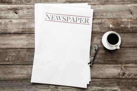 Zeitung und Kaffee auf hölzernem Hintergrund
