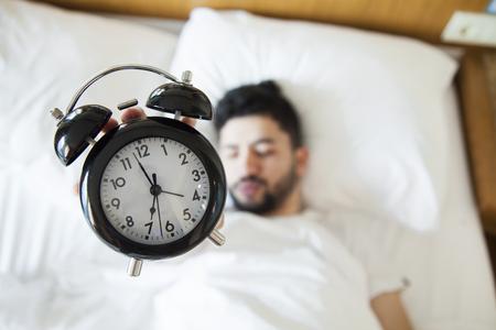 Hombre joven que le resulta difícil despertarse por la mañana