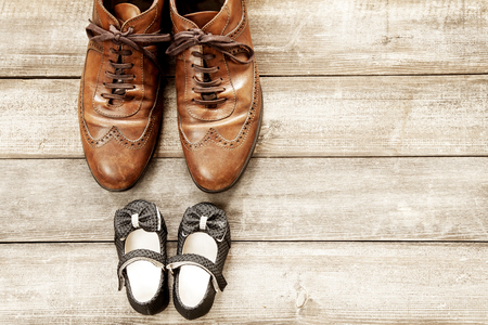 Father and girl brown shoes on wooden background, fathers day
