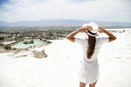 Natural travertine pools and terraces in Pamukkale. Cotton castle in southwestern Turkey, girl in white dress with hat natural pool Pamukkale Stock Photo