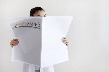 Woman reading newspaper on white background Stockfoto