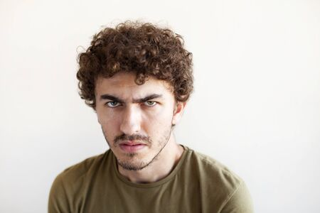 Portrait of young angry man on white background