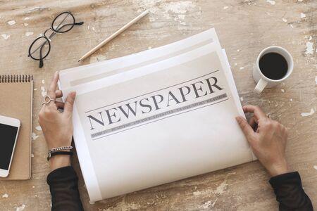 Femme lisant le journal sur fond de bois