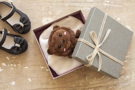 Bear in gift box on wooden background