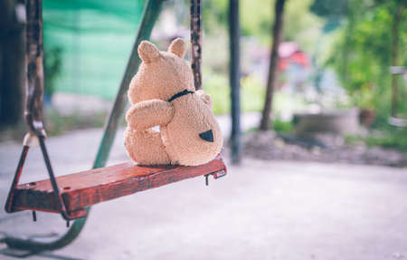 The brown dog doll playing is in the playground alone no kids.