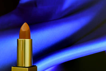 Close-up red brown lipstick on blue shiny cloth background . Tube and cover have gold color.