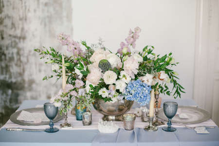 Silver candlestick and other elements of festive table wedding centerpieces decorations.