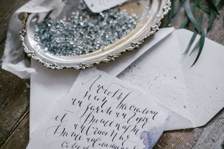 Graphic arts of beautiful wedding calligraphy cards and silver plate with silk ribbon on wood background.