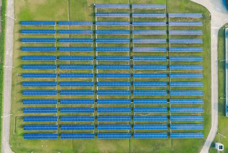 Aerial view of Solar Panels Farm with sunlight. Flying over the solar power plant at sunny day. Renewable energy power plant producing sustainable clean solar energy from the sun.
