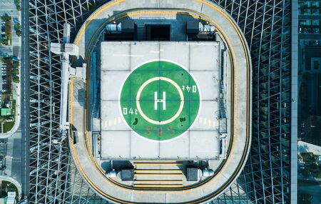 Aerial top view of helipad on the roof of a skyscraper iin downtown with cityscape view on sunny day Banque d'images