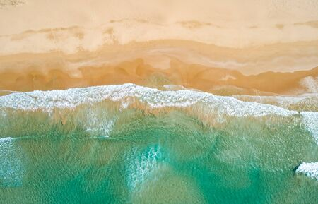 Aerial top view of turquoise ocean wave reaching the coastline. Banque d'images