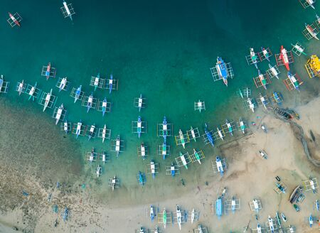 Aerial drone view of boats anchored in the bay with clear and turquoise water. Boats and yachts in the tropical lagoon. Tropical landscape.