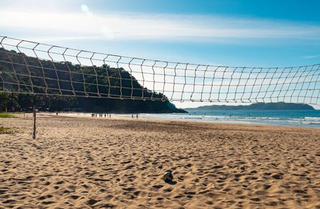 Beach Volleyball. Game ball under sunlight and blue sky with volleyball net