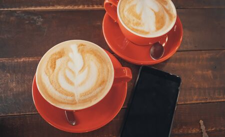 Two red cups of coffee with latte art on wooden desktop with the smartphone. Table in cafe. Top view. Banque d'images - 137868467
