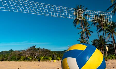 Beach Volleyball. Game ball under sunlight and blue sky with volleyball net on the background Banque d'images - 137868433