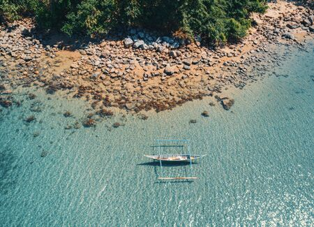 Aerial drone view of boat anchored in the bay with clear and turquoise water on sunny day. Boat in the tropical lagoon. Tropical landscape. El Nido, Palawan island, Philippines. Banque d'images - 137869269