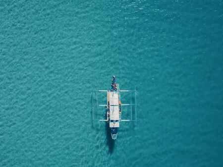 Aerial drone view of boat anchored in the bay with clear and turquoise water on sunny day. Boat in the tropical lagoon. Tropical landscape. El Nido, Palawan island, Philippines.