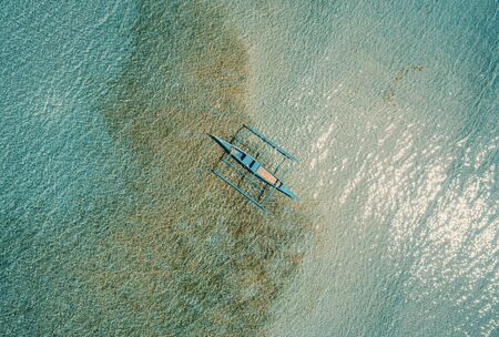 Aerial drone view of boat anchored in the bay with clear and turquoise water. Boat in the tropical lagoon. Tropical landscape.