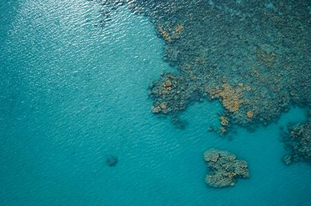 Aerial top view of the blue ocean and coral reef on sunny day. Sea surface.