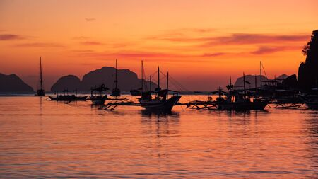 Beautiful sunset with silhouettes of philippine boats in El Nido, Palawan island, Philippines Banque d'images - 137872165