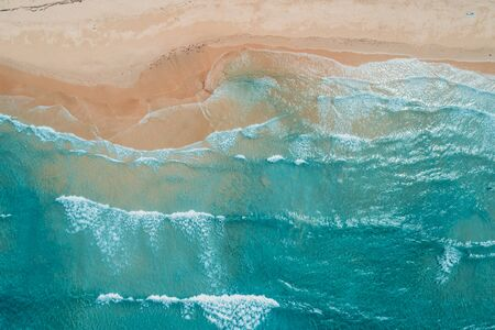 Aerial top view of turquoise ocean wave reaching the coastline. 스톡 콘텐츠