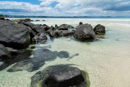 coolangatta: Spiaggia di Coolangatta con le rocce nere che fanno un bel contrasto Stock Photo