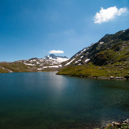 The lake in the Alps under the blue sky Фото со стока