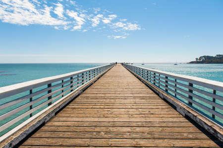 青空の下で海に木製の桟橋