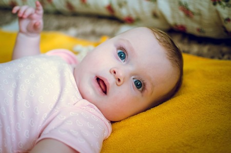top seven: Portrait of a 7 month cute baby girl and lying down on the bed looking very attentive Stock Photo