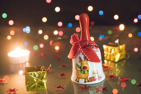 Christmas bell, small gifts and tea light candles on bokeh black backgound Stock Photo