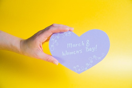 Female hand holding pink paper heart on golden background - Happy Womens Day Stock Photo