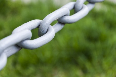metal mesh: Old gray strong mettalic chain against green grass field