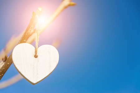 White vintage wooden heart hanging from tree branch against blue sky. Valentines Day. Blurred background and copy space.