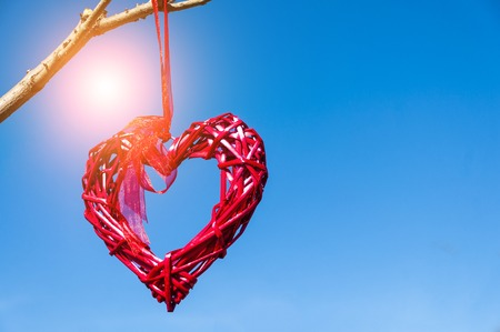 Red country wicker heart hanging from tree branch against blue sky; Valentines Day and love concept with copy space.